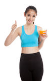 Beautiful Asian healthy girl drinking  orange juice thumbs up Stock Photography