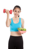 Beautiful Asian healthy girl with dumbbell and salad Stock Images