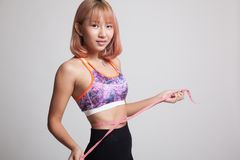 Beautiful Asian healthy girl measuring her waist. Beautiful Asian healthy girl measuring her waist on gray background Stock Photos