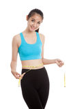 Beautiful Asian healthy girl measuring her waist. Isolated on white background Stock Image