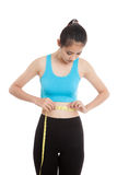 Beautiful Asian healthy girl measuring her waist. Isolated on white background Royalty Free Stock Photos