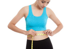 Beautiful Asian healthy girl measuring her waist. Isolated on white background Royalty Free Stock Photo