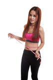 Beautiful Asian healthy girl measuring her waist. Royalty Free Stock Photos
