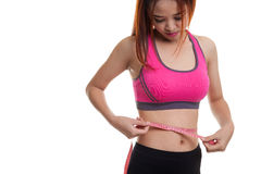 Beautiful Asian healthy girl measuring her waist. Royalty Free Stock Photo