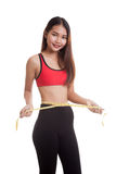 Beautiful Asian healthy girl measuring her waist. Royalty Free Stock Image