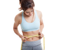 Beautiful Asian healthy girl measuring her waist. Royalty Free Stock Photography