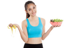 Beautiful Asian healthy girl with measuring tape and salad Royalty Free Stock Photo