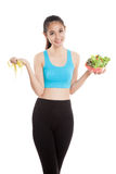 Beautiful Asian healthy girl with measuring tape and salad Stock Photo