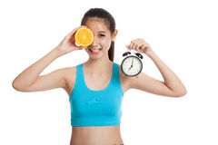 Beautiful Asian healthy girl with orange and clock Royalty Free Stock Photos