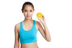 Beautiful Asian healthy girl with orange fruit licks her lips Stock Image