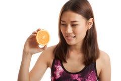 Beautiful Asian healthy girl with orange fruit licks her lips. Stock Photo
