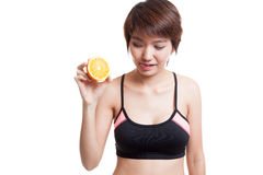 Beautiful Asian healthy girl with orange fruit licks her lips. Royalty Free Stock Images