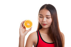 Beautiful Asian healthy girl with orange fruit licks her lips. Royalty Free Stock Image