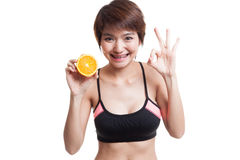 Beautiful Asian healthy girl show OK with orange fruit. royalty free stock photography