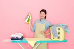 Asian housewife holding a home ironing Royalty Free Stock Photo