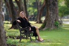Beautiful Asian lady in black dress, posing in the park, greener Stock Image