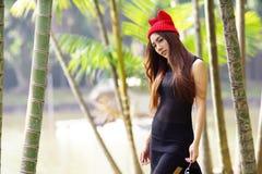 Beautiful Asian lady in black dress, posing in the park, greener Stock Images