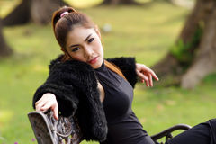 Beautiful Asian lady in black dress, posing in the park, greener Royalty Free Stock Images