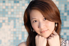 Beautiful Asian lady in front of mosaic and smile Stock Photos