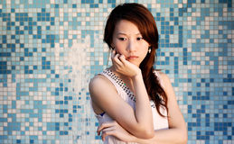 Beautiful Asian lady in front of mosaic and think Royalty Free Stock Photo