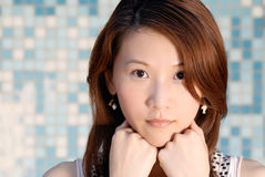 Beautiful Asian lady in front of mosaic and watch Stock Photo