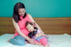 A beautiful Asian lady mother is pregnant. Take a big headset Come to the stomach Let the child in the belly listen Have a little royalty free stock photography