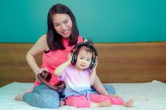 A beautiful Asian lady mother is pregnant. Take a big headset Come to the stomach Let the child in the belly listen Have a little royalty free stock image
