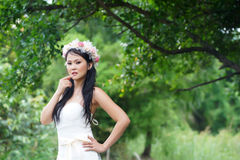 Beautiful Asian lady white bride dress, posing in the forest Stock Photography