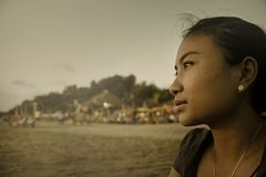 Beautiful Asian lonely woman looking to infinity lost in her thoughts sad and thoughtful sitting on sand beach Stock Photography