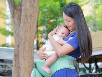 Beautiful Asian mother hugging her infant on ergonomic baby carrier in the garden.  stock image