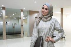 Beautiful asian muslim woman with hand at waist holding laptop Stock Photos