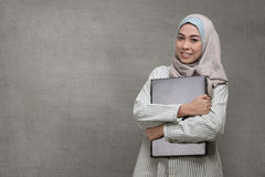 Beautiful asian muslim woman holding laptop. Against concrete background Royalty Free Stock Images