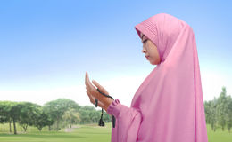 Beautiful asian muslim woman praying with prayer beads. At outdoor Stock Photos