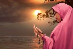 Beautiful asian muslim woman praying with prayer beads. During sunset Royalty Free Stock Photo