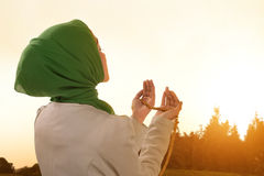 Beautiful asian muslim woman praying with prayer beads. During sunset Royalty Free Stock Images