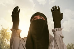 Beautiful asian muslim woman in traditional dress praying Stock Photos