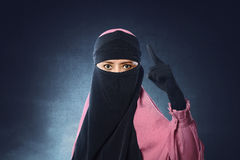 Beautiful asian muslim woman in veil pointing with upset eyes Stock Photos