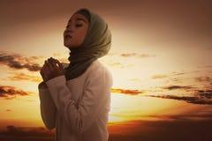 Beautiful asian muslim woman in veil praying to god Stock Photo