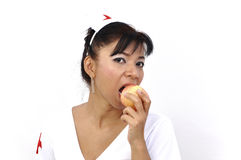 Beautiful Asian nurse eats apple Royalty Free Stock Photos