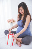 Beautiful asian pregnant woman accepting a gift, exciting to ope Royalty Free Stock Photography