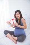 Beautiful asian pregnant woman accepting a gift, exciting to ope. A portrait of a beautiful asian pregnant woman accepting a gift, exciting to open it royalty free stock photography