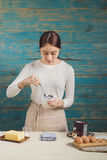 Beautiful asian smiling while tasting her homemade muffins Royalty Free Stock Photography