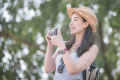 Beautiful asian solo tourist woman enjoy taking photo by retro camera at tourist sightseeing spot. stock images