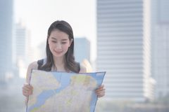 Beautiful asian solo tourist woman looking at the map searching for tourists sightseeing spot. stock photo