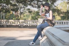 Beautiful asian solo tourist woman reading the travel guide book searching for for tourists sightseeing spot. Vacation travel in summer stock photo