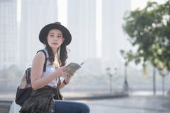 Beautiful asian solo tourist woman reading the travel guide book searching for for tourists sightseeing spot. Vacation travel in summer stock image