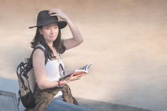 Beautiful asian solo tourist woman reading the travel guide book searching for for tourists sightseeing spot. Vacation travel in summer royalty free stock image