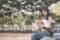 Beautiful asian solo tourist woman reading the travel guide book searching for for tourists sightseeing spot. Vacation travel in summer stock photography