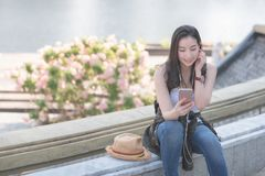 Beautiful asian solo tourist woman relaxing and enjoying listening the music on a smartphone in urban city downtown royalty free stock photo