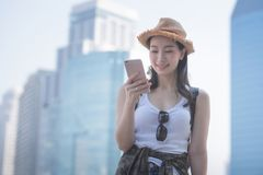 Beautiful asian solo tourist woman smiling and looking at mobile phone for searching tourists sightseeing spot royalty free stock photography